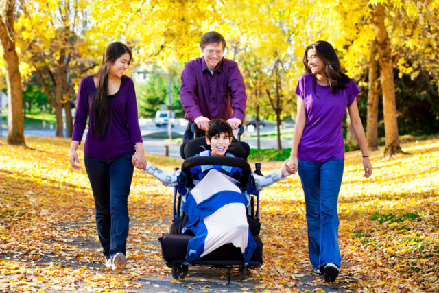 A family with a child in wheelchair and two sisters walking among autumn leaves