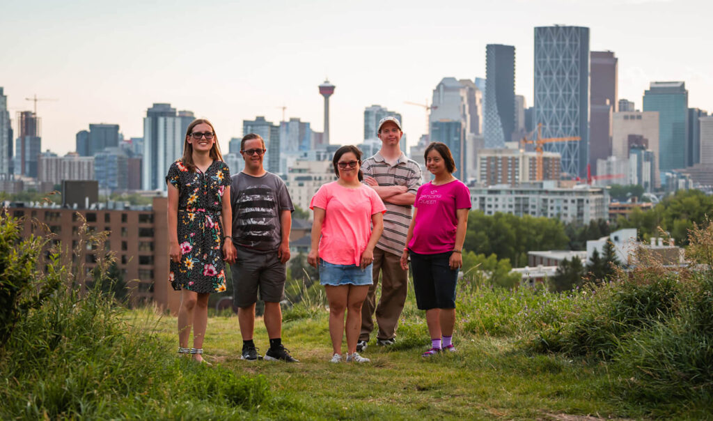 5 people standing on grass with the city in the background.